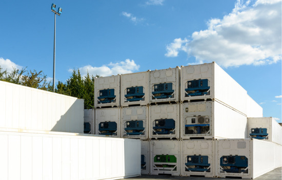 Refrigerated containers for Cedar Rapids IA stacked in a shipping yard. Trees and a blue sky with clouds peek out behind.