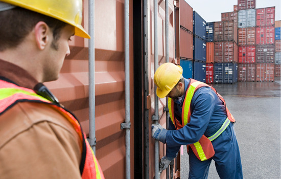 Man watches a worker in a construction hat shut one of several refrigerated containers in Rockford IL
